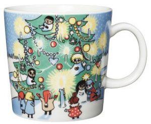 Joulumuki Muumimukin kuvitus on talvinen, ja siinä Muumilaakson väki iloistee joulukuusen ympärillä.